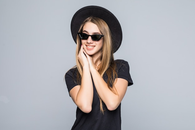 Jonge mooie lachende dame in briljante zonnebril gekleed in zwarte hoed, zwart t-shirt en donkere broek geïsoleerd op grijze achtergrond houdt handen onder de kin samen