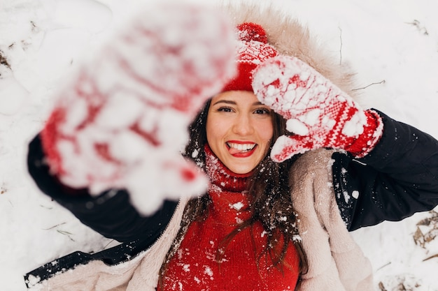 Jonge mooie lachende gelukkige vrouw in rode wanten en gebreide muts dragen winterjas liggend in park in de sneeuw, warme kleren, van bovenaf bekijken