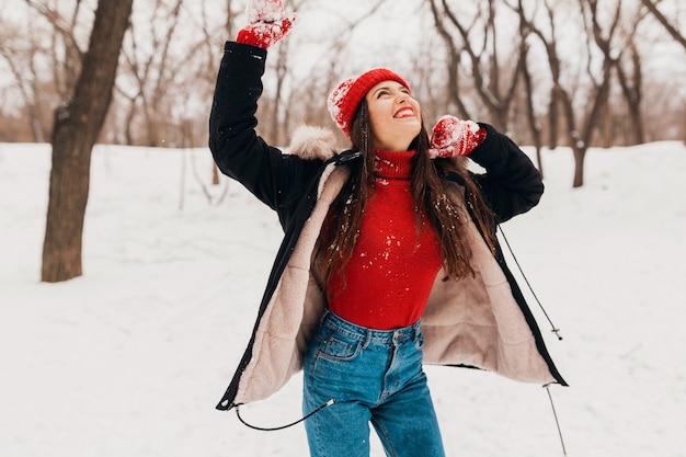 Jonge mooie lachende gelukkige vrouw in rode wanten en gebreide muts dragen winterjas wandelen in park in de sneeuw, warme kleren, plezier