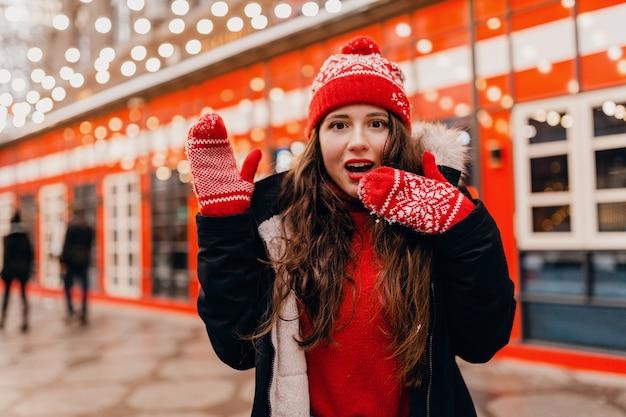 Jonge mooie lachende gelukkige vrouw in rode wanten en gebreide muts met geschokt verbaasd gezicht dragen winterjas wandelen in stad straat, warme kleren