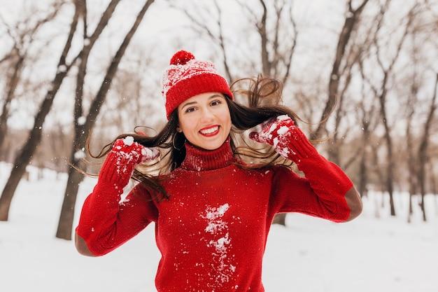 Jonge mooie lachende gelukkige vrouw in rode wanten en muts dragen gebreide trui wandelen in het park in de sneeuw, warme kleren, plezier, lang haar zwaaien