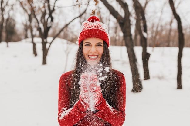 Jonge mooie lachende gelukkige vrouw in rode wanten en muts dragen gebreide trui wandelen in park in de sneeuw, warme kleren, plezier