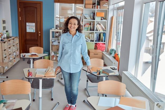 Jonge mooie lachende leraar portret in school klas