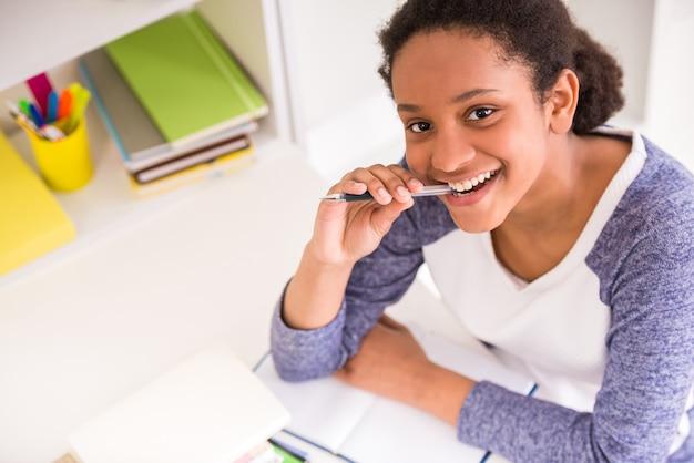Jonge mooie lachende mulat schoolmeisje zittend aan tafel.
