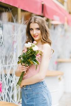 Jonge mooie lachende vrouw in modieuze zomerkleren. een sexy zorgeloze vrouw poseert tegen de achtergrond van de straat met een boeket rozen. positief buitenmodel