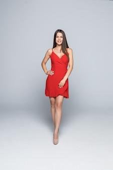 Jonge mooie lachende vrouw in rode jurk op witte muur