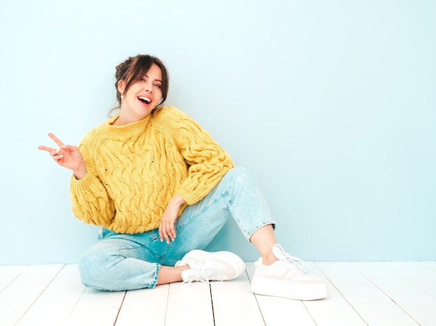 Jonge mooie lachende vrouw in trendy zomer gele hipster trui en jeans