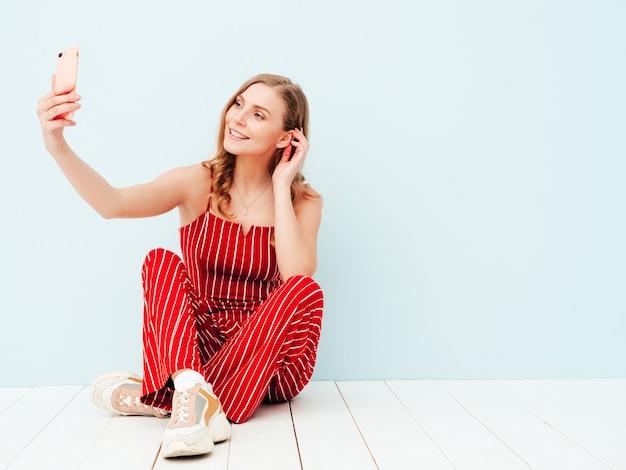 Jonge mooie lachende vrouw in trendy zomerkleren. sexy zorgeloze vrouw poseren in de buurt van lichtblauwe muur in studio