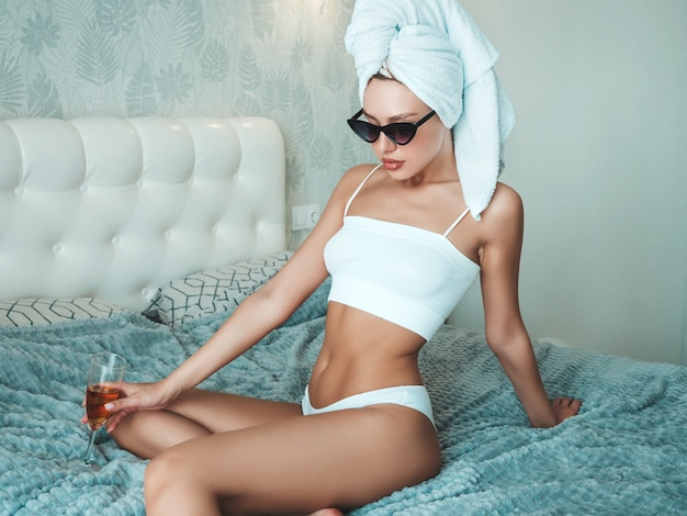 Jonge mooie lachende vrouw in witte lingerie en handdoek op hoofd