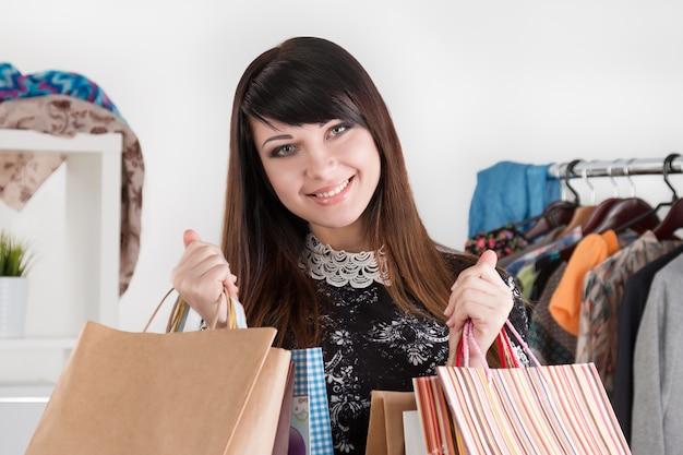 Jonge mooie lachende vrouw met papieren zakken met aankopen