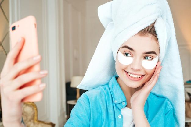 Jonge mooie lachende vrouw met patches onder de ogen. zorgeloos model poseren in chique appartement of hotelkamer in wit interieur