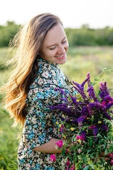 Jonge mooie langharige blonde vrouw van europees uiterlijk met een bloeiend boeket van wilde bloemen...