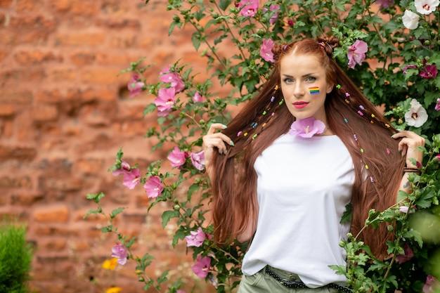Jonge mooie langharige brunette meisje met lgbt regenboog op haar gezicht poseren in bloeiende bloemen