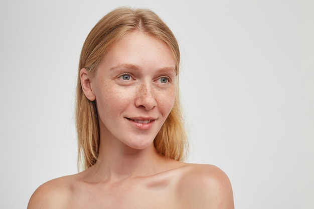 Jonge mooie langharige dame met natuurlijke make-up kijkt positief opzij en lacht aangenaam, staande over witte muur met blote schouders
