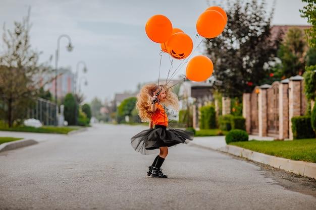 Jonge mooie langharige meid in kostuum als een kleine heks die op straat speelt met pompoenballonnen tijdens zonsopgang. vakantieconcept.
