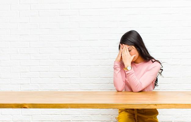 Jonge mooie latijns-vrouw die de ogen bedekt met handen met een droevige, gefrustreerde blik van wanhoop, huilend, zijaanzicht dat voor een tafel zit