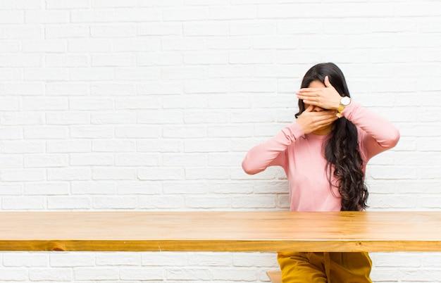 Jonge mooie latijns-vrouw die gezicht bedekt met beide handen nee zeggen tegen de camera! afbeeldingen weigeren of foto's voor een tafel verbieden