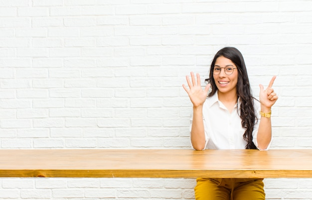 Jonge mooie latijns-vrouw glimlacht en kijkt vriendelijk, toont nummer zeven of zevende met hand vooruit, aftellen zitten voor een tafel
