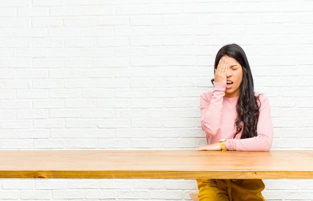 Jonge mooie latijns-vrouw op zoek slaperig, verveeld en geeuwen, met een hoofdpijn en een hand voor de helft van het gezicht zit achter een tafel