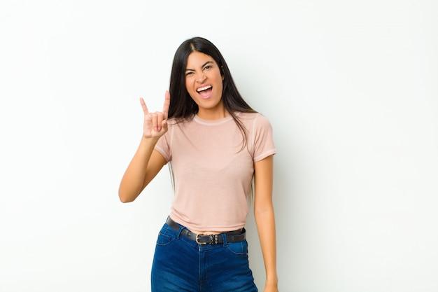 Jonge mooie latijns-vrouw voelt zich gelukkig, leuk, zelfverzekerd, positief en rebels, het maken van rock of heavy metal bord met hand tegen vlakke muur