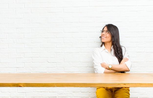 Jonge mooie latijns-vrouw voelt zich gelukkig, trots en hoopvol, vraagt zich af of denkt, kijkend naar copyspace met gekruiste armen voor een tafel zitten