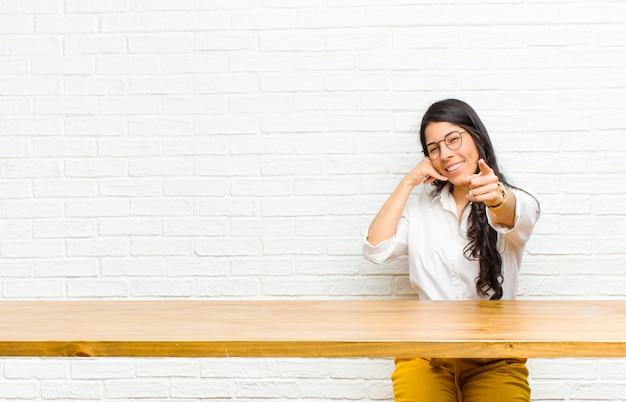 Jonge mooie latijns-vrouw vrolijk glimlachen en wijzend naar de camera tijdens het bellen u later gebaar, praten over telefoon zit achter een tafel