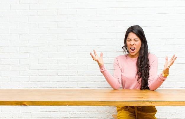 Jonge mooie latijns-vrouw woedend schreeuwen gevoel gestrest en geïrriteerd met handen omhoog in de lucht zeggen waarom ik
