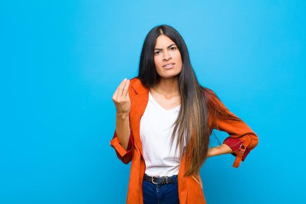 Jonge mooie latijnse vrouw die kapsel of geldgebaar maakt en zegt dat je je schulden moet betalen! tegen een vlakke muur