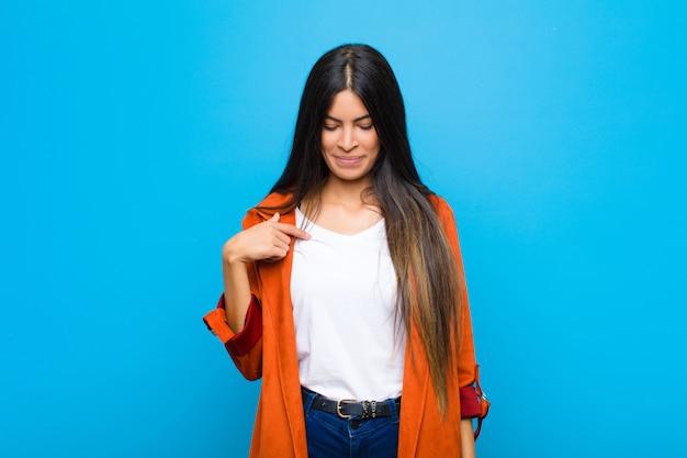 Jonge mooie latijnse vrouw die vrolijk en nonchalant glimlacht, naar beneden kijkt en naar borst wijst tegen vlakke muur