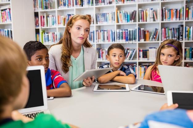 Jonge mooie leraar die les hebben aan kinderen met hun tablet