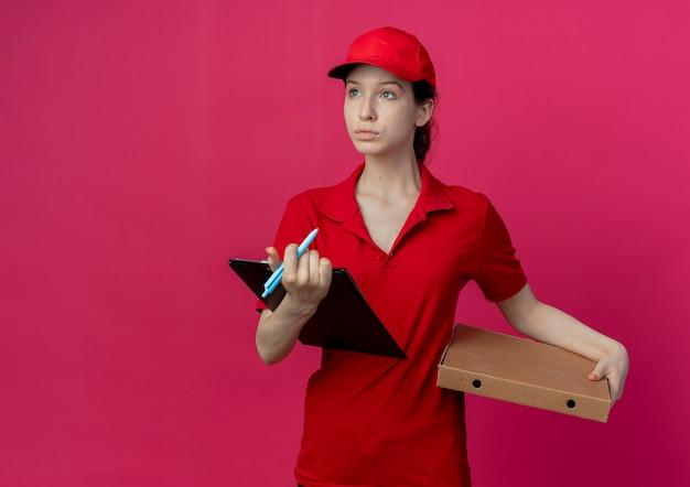 Jonge mooie levering meisje in rood uniform en pet houden pizza pakket pen en klembord kijken kant geïsoleerd op karmozijnrode achtergrond met kopie ruimte