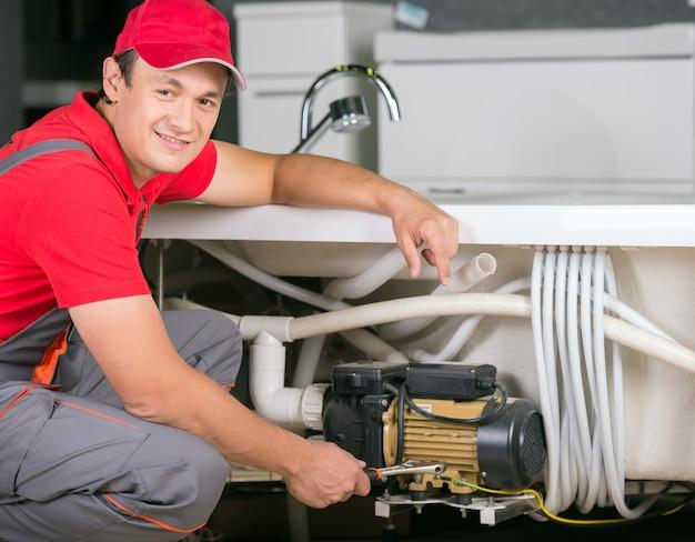 Jonge mooie loodgieter op het werk.