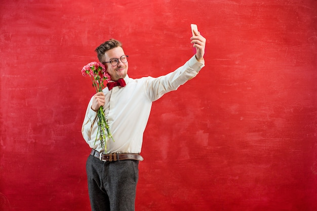 Jonge mooie man met bloemen en telefoon