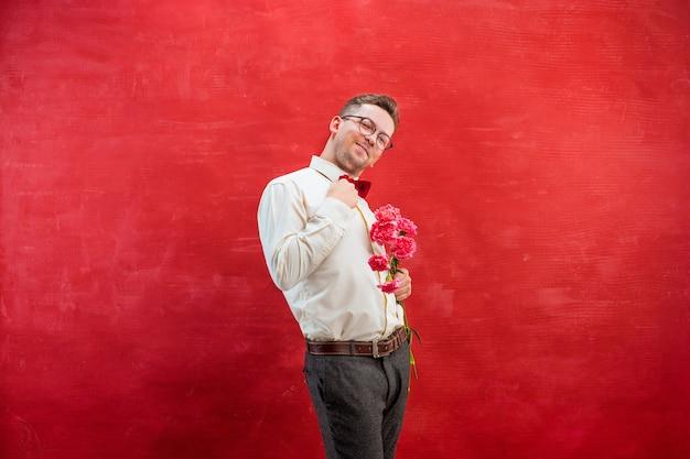 Jonge mooie man met bloemen op rode studio achtergrond