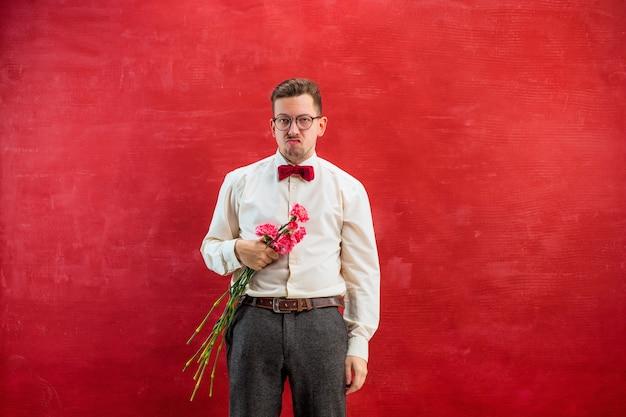 Jonge mooie man met bloemen op rode studio
