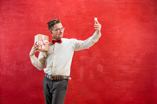 Jonge mooie man met cadeau en telefoon