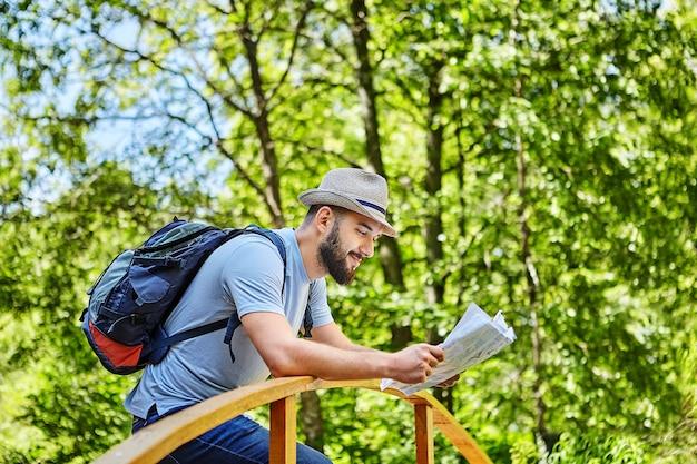 Jonge mooie man met hoed op zijn hoofd en rugzak controleert kaart op brug in bos.