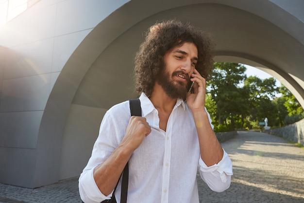 Jonge mooie man met weelderige baard en bruin krullend haar poseren over boog in groen park op zonnige warme dag, bellen met zijn mobiele telefoon