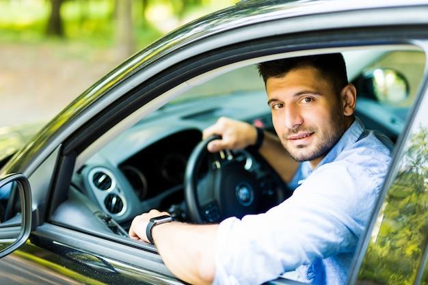 Jonge mooie man zit in een auto