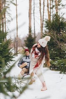 Jonge mooie meid heeft plezier met haar geliefde vriendje rijden op een slee met geschenken in een winter naaldbos. een park met kerstbomen op de achtergrond. kerststemming. verven.