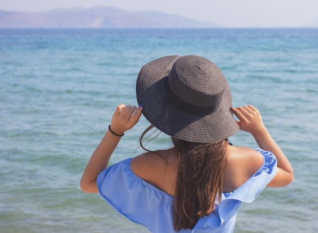 Jonge mooie meid in een hoed kijkt naar de zee