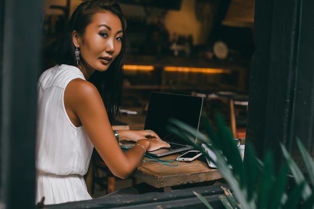 Jonge mooie meid maakt gebruik van een laptop in het café, surfen op het internet