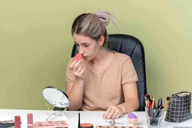 Jonge mooie meid zit aan bureau met make-up tools die tonercrème afvegen met spons geïsoleerd op olijfgroene muur