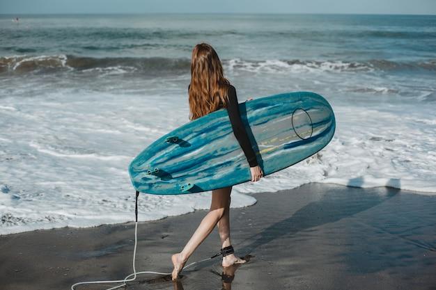 Jonge mooie meisje die zich voordeed op het strand met een surfplank, vrouw surfer, oceaan golven