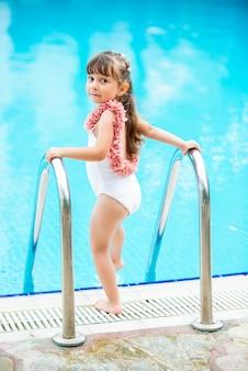 Jonge mooie meisje in een badpak water plons maken bij het zwembad. genieten van de zomer en plezier hebben. vakantie stemming.