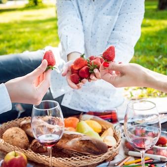 Jonge mooie meisjes die aardbeien in het park eten