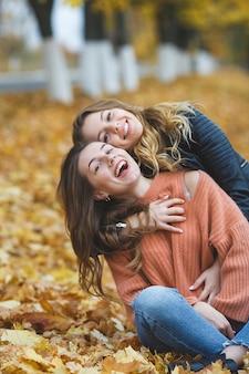 Jonge mooie meisjes die pret in openlucht op de herfstachtergrond hebben. vrolijke vrienden in de herfst tijd
