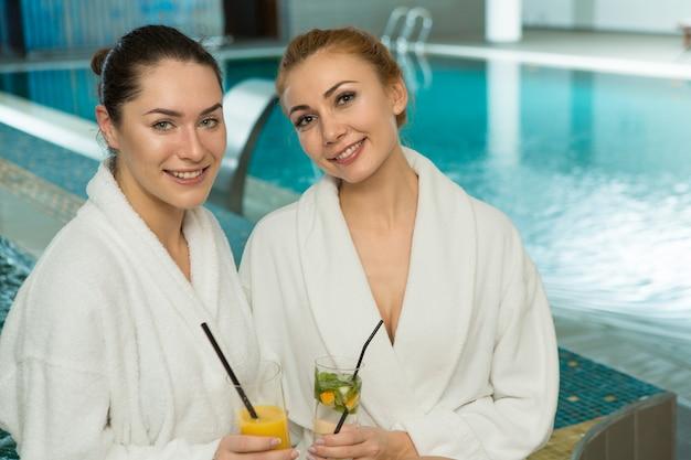 Jonge mooie meisjes in badstof gewaden ontspannen bij het zwembad