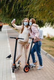Jonge mooie meisjes in maskers rijden in het park op een elektrische scooter op een warme herfstdag en nemen selfies. wandeling in het park.