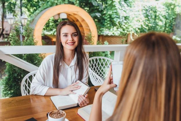Jonge mooie meisjes leren in het café op zomerterras met nieuwe boeken.